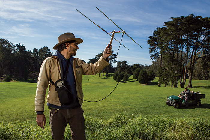 Ecologist Jonathan Young holds up an antenna that helps him track radio-collared coyotes at the Presidio Golf Course in San Francisco. (Photo by Sebastian Kennerknecht, Urban Coyote Initiative)