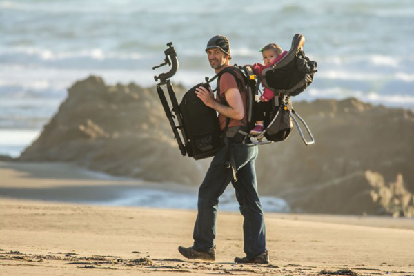 Wildlife photographer Daniel Dietrich and child in carrier at Point Reyes' Kehoe Beach.